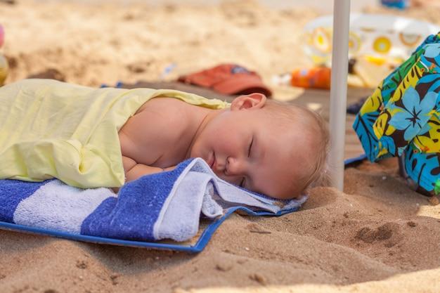 Słodki chłopczyk śpi na plaży, zmęczony zabawą na plaży