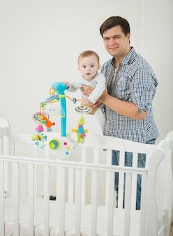 Słodki chłopczyk stojący w łóżeczku i bawiący się z ojcem