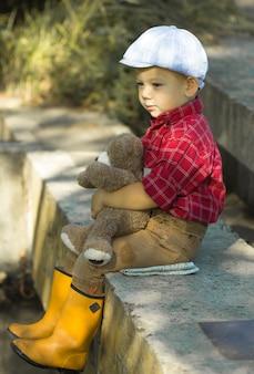 Słodki chłopczyk w żółtych gumowych butach dobrze się bawi, skacząc w kałużach, wodując łódkę po wiosennym deszczu