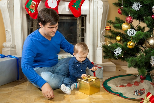 Słodki chłopczyk z ojcem otwiera prezenty świąteczne na podłodze w salonie