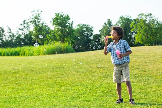 Słodki chłopiec afro robi bąbelki na słonecznej polanie