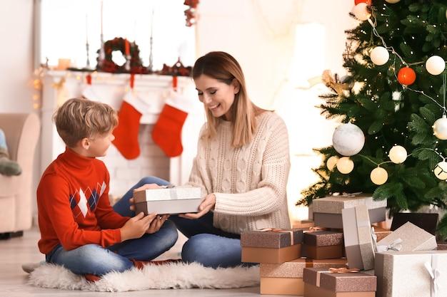 Słodki chłopiec i jego mama z prezentami świątecznymi w domu