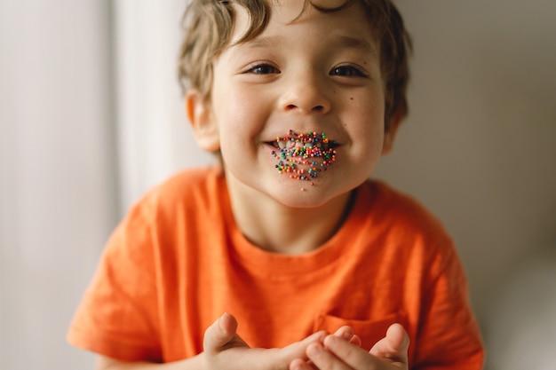 Słodki chłopiec je i bawi się wielkanocną posypką