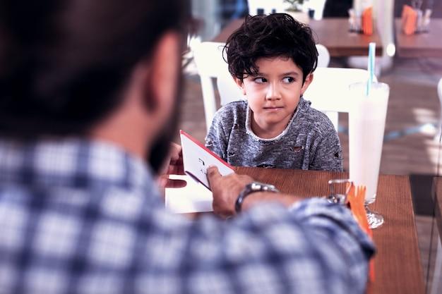 Słodki chłopiec. mały śliczny ciemnowłosy chłopiec ubrany w stylowy sweter, słuchając swojego nauczyciela języka obcego