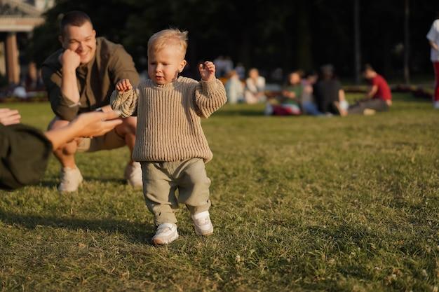Słodki chłopiec rasy kaukaskiej uczący się chodzić po trawniku w parku jego matka otwiera szeroko ramiona, by go złapać