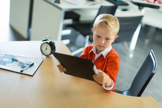 Słodki chłopiec siedzi przy biurku w biurze i używa komputera typu tablet