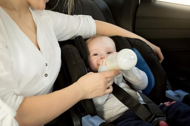 Słodki chłopiec siedzi w foteliku samochodowym z butelką