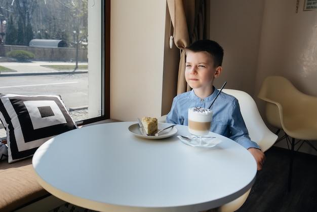 Słodki chłopiec siedzi w kawiarni i patrzy na ciasto i kakao z bliska. dieta i prawidłowe odżywianie.