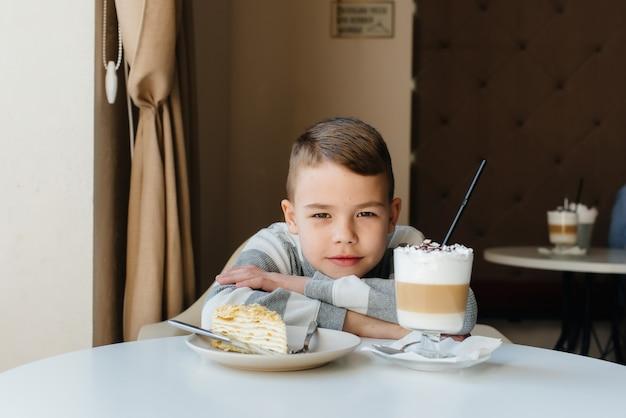 Słodki chłopiec siedzi w kawiarni i patrzy na zbliżenie ciasta i kakao. dieta i prawidłowe odżywianie.