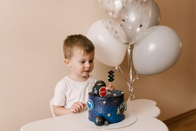 Słodki chłopiec świętuje swoje urodziny i je pyszne piękne ciasto, zdjęcie dziecka z balonami