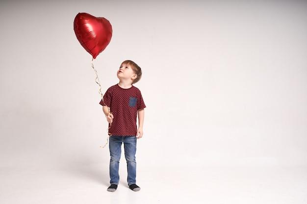 Słodki chłopiec trzyma balon z czerwonym sercem walentynki lub koncepcja medyczna dla dzieci opieki zdrowotnej