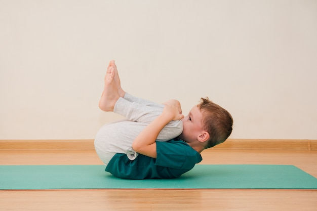 Słodki chłopiec uczy się jogi na siłowni