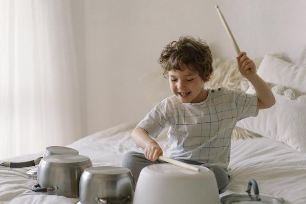 Słodki chłopiec używa drewnianych patyczków do uderzania rondli ustawionych jak zestaw perkusyjny.