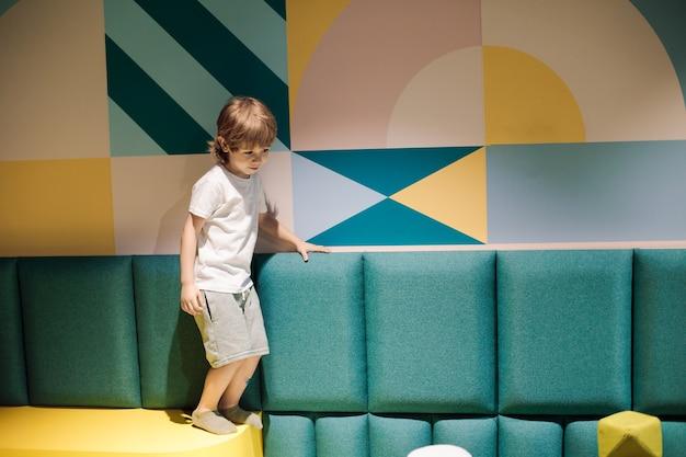 Słodki chłopiec w centrum gier balansuje na miękkich powierzchniach. koloroterapia w ośrodkach zdrowia i szkolenia dzieci. organizacja sal zabaw dla dzieci. nowoczesne instytucje dziecięce.