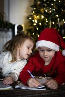 Słodki chłopiec w czerwonym swetrze i czerwonej czapce mikołaja pisze list do świętego mikołaja