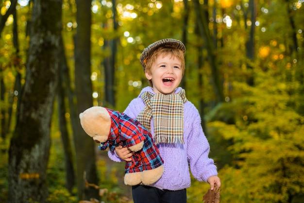 Słodki chłopiec w jesiennym parku jesień dzieciak mały chłopiec bawi się z misiem w parku jesień czas mały chłopiec