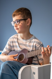 Słodki chłopiec w okularach uczy się grać na gitarze ukulele w domu, w swoim pokoju.