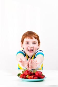 Słodki chłopiec z rudymi włosami zjada dojrzałe truskawki, chłopiec z jagodami podczas deseru