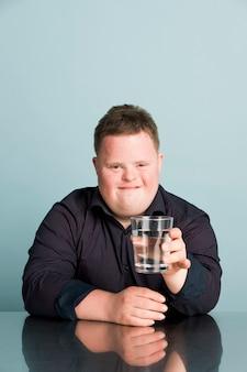 Słodki chłopiec z zespołem downa trzymający szklankę wody