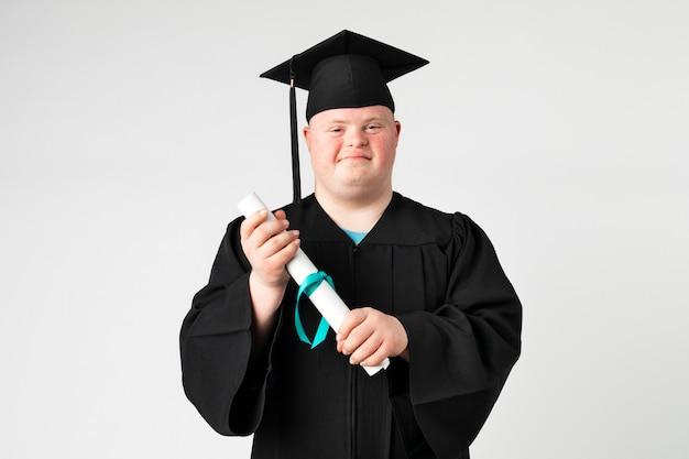 Słodki chłopiec z zespołem downa w sukni na zakończenie szkoły