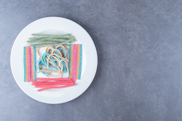 Słodki cukierek laski na drewnianym talerzu na marmurowym stole.