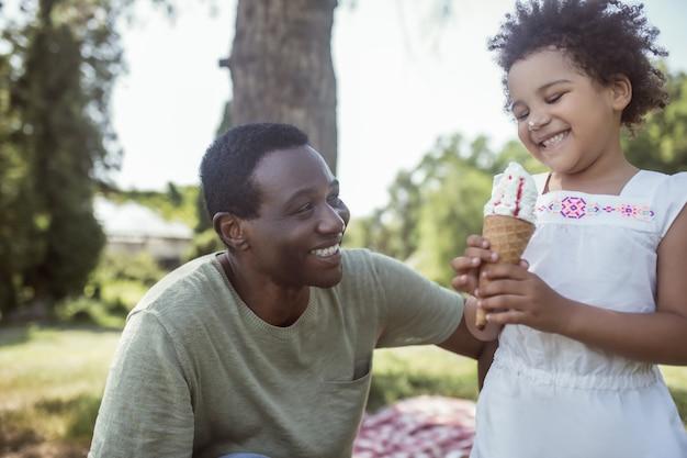 Słodki czas. słodki dzieciak z kręconymi włosami je lody i spędza czas z tatą