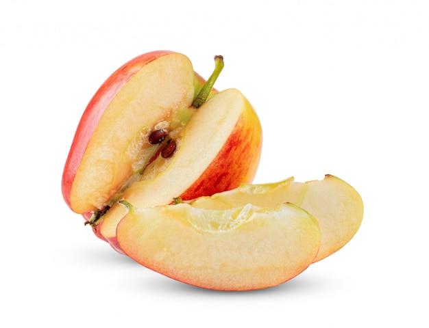 Słodki czerwony jabłko z plasterkiem na bielu stole.