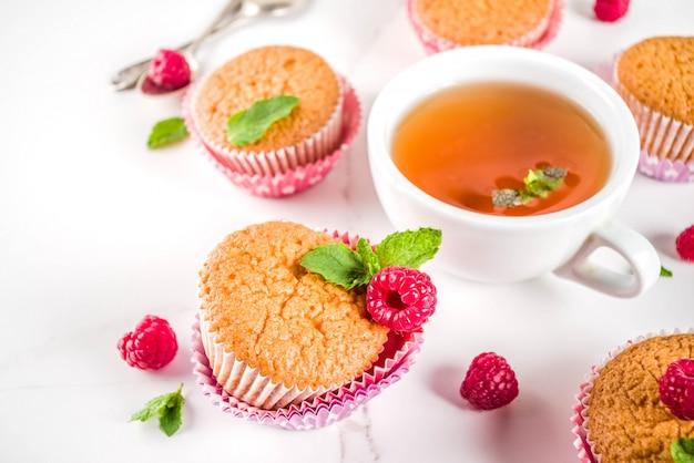 Słodki deser, domowej roboty muffin z dżemem malinowym, podany z herbatą, świeżymi malinami i miętą