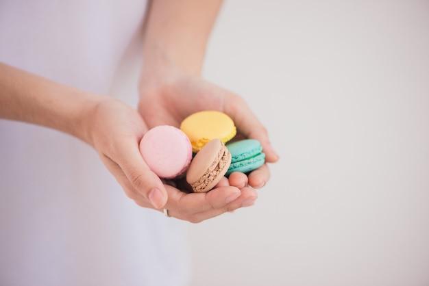 Słodki deser. kolorowe makaroniki na kobiecych rękach.