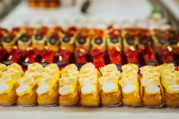 Słodki deser. linie smacznych eklerów o różnych smakach owocowych i czekoladowych