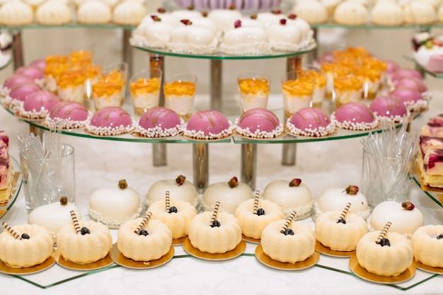 Słodki deser lub batonika. stół z różnymi słodyczami na imprezę. wakacyjny bufet z babeczkami i innymi deserami. macaron, babeczki, ptasie mleczko z bliska