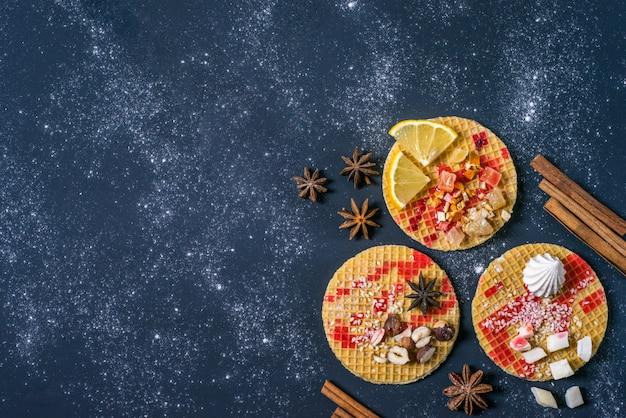 Słodki deser na ciemności. tradycyjne śniadanie z gaufre, gofrem, chrupiącym waflem z orzechami, owocami i syropem.