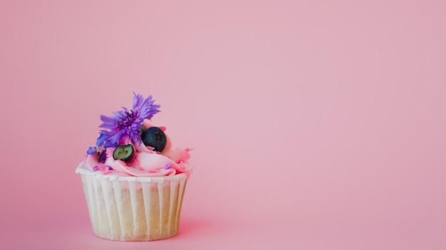 Słodki deser na różowej kopii przestrzeni. babeczka ze śmietaną, piękna i pyszna.