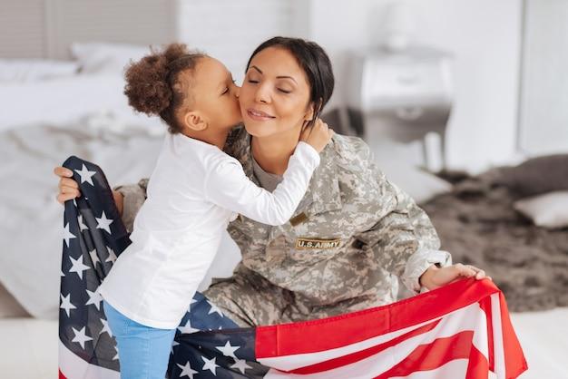 Słodki dom. czuła troskliwa piękna kobieta czuje się emocjonalnie całowana przez córkę i trzyma flagę w dłoniach