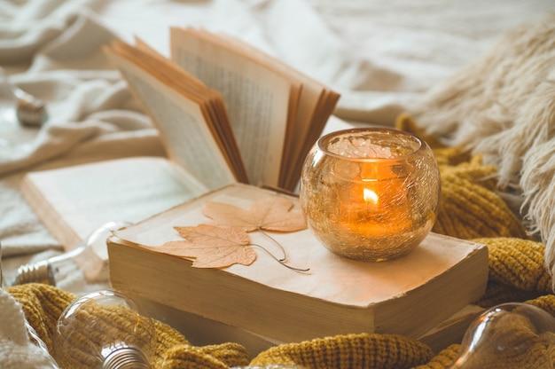 Słodki dom. martwa natura w mieszkaniu wnętrza salonu. swetry i świeca, jesienne dekoracje na książkach. czytaj, odpoczywaj. przytulna koncepcja jesień lub zima.