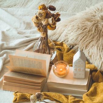 Słodki dom. martwa natura w mieszkaniu wnętrza salonu. wazon i świeca suszonych kwiatów, dekoracje jesienne na książkach. czytaj, odpoczywaj. przytulna koncepcja jesień lub zima.