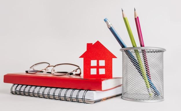 Słodki dom. oszacowanie i opłacenie podatku od nieruchomości. makieta z czerwonym domem, notatnikiem i naklejką w przestrzeni kopii na białym tle