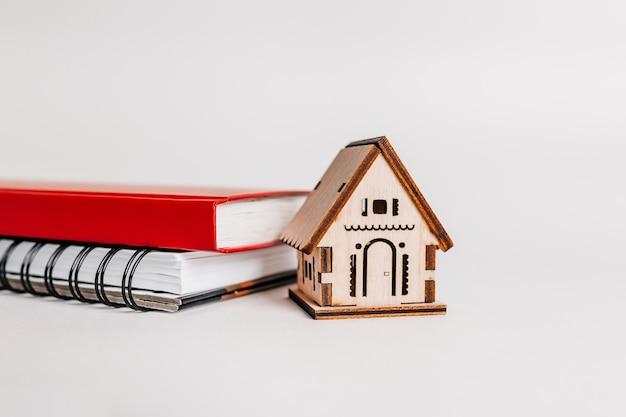 Słodki dom. szacowanie i płacenie podatku od nieruchomości. makieta z czerwonym domem, notatnik