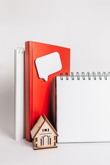 Słodki dom. szacowanie i płacenie podatku od nieruchomości. makieta z czerwonym domkiem, notatnikiem i naklejką