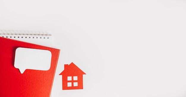 Słodki dom. szacowanie, płacenie podatku od nieruchomości. makieta z czerwonym domem, notatnikiem i naklejką w przestrzeni kopii