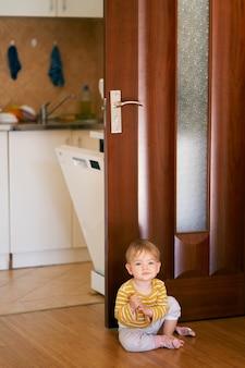 Słodki dzieciak w pasiastej bluzce siedzi na podłodze w kuchni