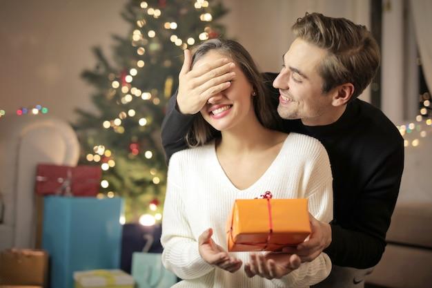 Słodki facet daje jej dziewczynie swój świąteczny prezent dla niej