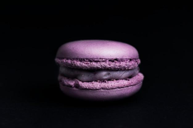 Słodki fioletowy makaronik na czarnym tle