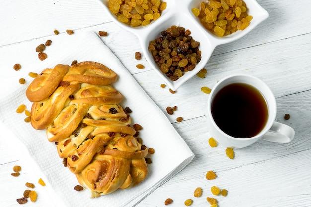 Słodki galonowy chleb z rodzynkami na kuchennym ręczniku na białym drewnianym tle.
