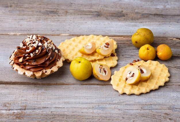 Słodki gofr i tort z śmietanką na drewnianym tle