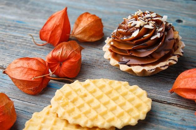 Słodki gofr, tort z śmietanką i pęcherzycą na drewnianym tle