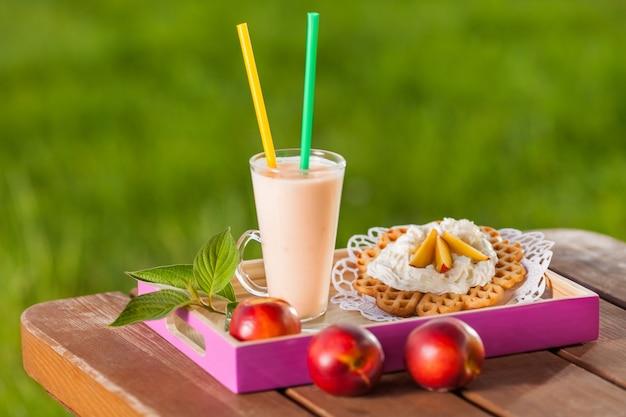 Słodki gofr z koktajlem brzoskwiniowym w letni dzień