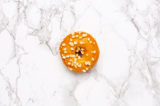 Słodki karmelowy pączek na marmurowej powierzchni odosobnionym mieszkaniu nieatutowym, minimalizm, jedzenie