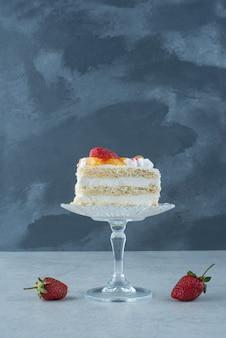 Słodki kawałek ciasta na szklanym talerzu i dwie czerwone truskawki. wysokiej jakości zdjęcie