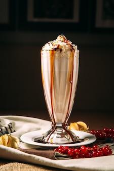Słodki koktajl mleczny ozdobiony syropem czekoladowym